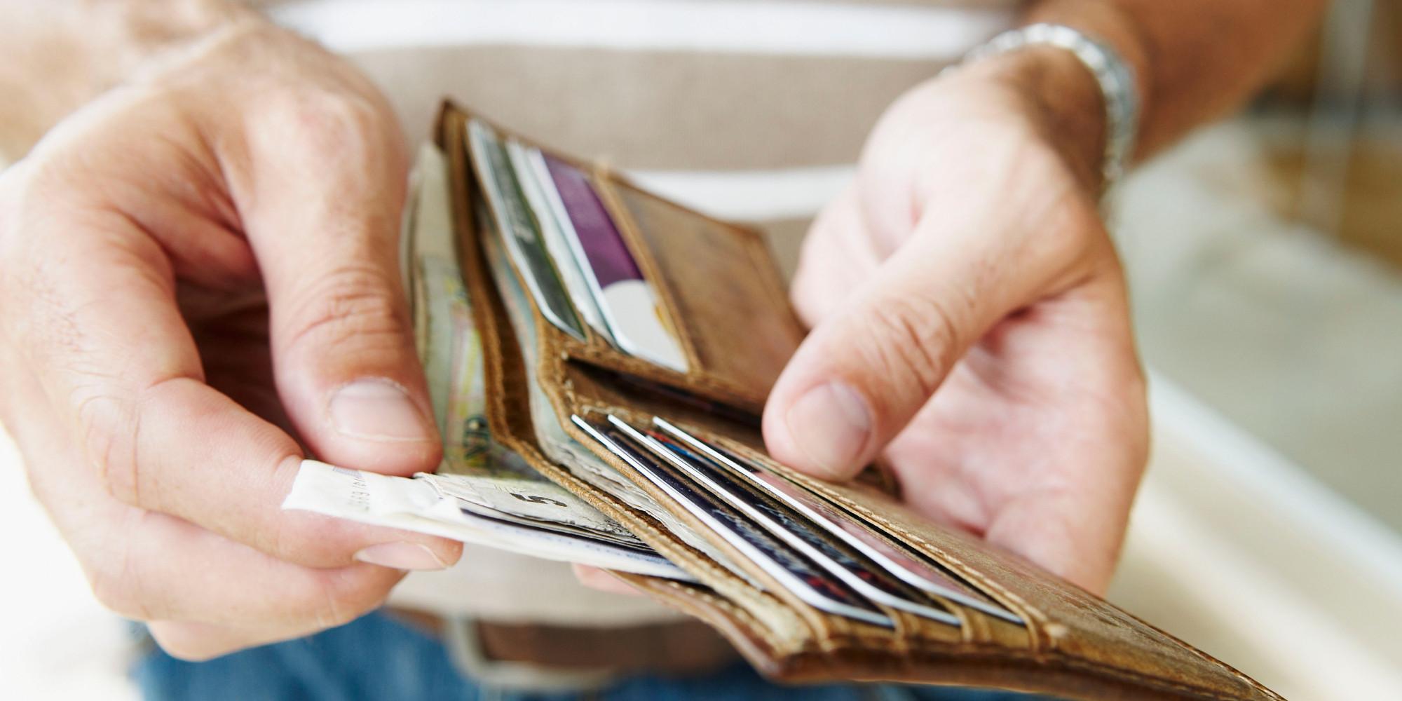 B0FR95 Man removes cash from wallet